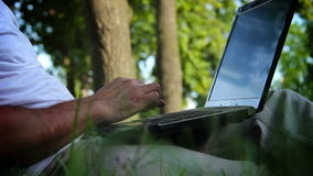 Business man working on a notebook in the park. Stock Images