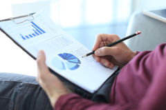 Business man working at office with graph data documents on his desk. Stock Photos