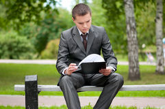 Business man working with papers at park. Student Royalty Free Stock Images