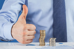 Business man working at the table and showing thumb up sign Royalty Free Stock Images