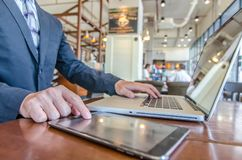 Business man working using Ipad while working with laptop. Businessman working at his desk in coffee shop Royalty Free Stock Image