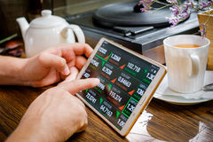 Business man works with foreign exchange rates. On tablet pc in cafe Royalty Free Stock Photo
