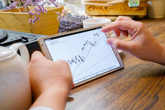 Business man works with graph on tablet pc. In cafe Stock Image