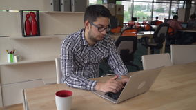 Business man works at the modern big open space studio. Handsome man mixed race typing on the computer at his working place. On the background colleagues work stock video footage