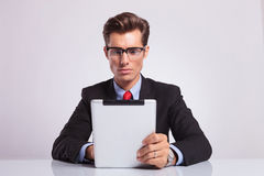Business man works on tablet. Young business man sitting at the desk and working on his tablet with a serious look on his face Stock Photo