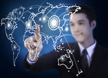 Business man with world map graphic screen. Business man pressing a world map touchscreen Royalty Free Stock Images