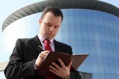 Business man writing. Business man in the middle of writing up the business building Royalty Free Stock Photo
