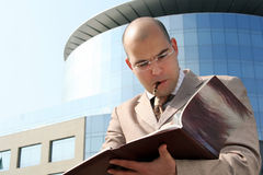 Business man writing. Business man in the middle of writing up the business building holding pen in mouth Stock Photos