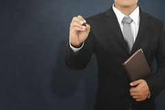 Business man writing and holding book on blank wall for text and Royalty Free Stock Photo