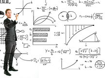 Business man writing math and graphs Royalty Free Stock Image