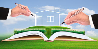Business man writing new house on beautiful green field Royalty Free Stock Photo
