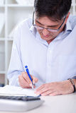 Business man writing note. Business man sitting in office with laptop writing note Stock Photo