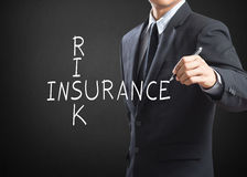 Business man writing Risk Insurance Stock Photo