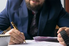 Business man writing a treaty or contract at the table and working on documents in the office,business concept. Business man lawyer with wristwatch writing Stock Photo