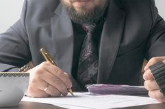 Business man writing a treaty or contract at the table and working on documents in the office,business concept. Stock Image