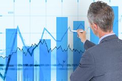 Business man writing on wall with financial graphs. Digital composite of Business man writing on wall with financial graphs Royalty Free Stock Image