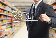 Business man writing word retail. In the supermarket Stock Images