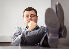 Business man. Young business man with legs on desk. Shallow depth of field Stock Photography