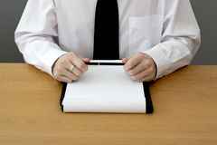 Business management. Man in shirt and tie sat at a table for a business meeting, holding a pen stock photo