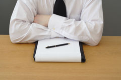 Business management meeting. Man in shirt and tie sat at a table for a business meeting, with a pen and folder stock photography