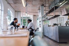 Business manager and chef talking in restaurant. Restaurant owner and cook sitting at table and having conversation royalty free stock image