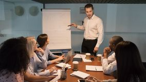 Business manager coach speaker giving corporate presentation pointing at flipchart stock photos