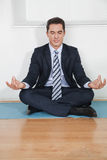 Business manager doing yoga. Relaxed business manager doing yoga in his office Stock Photos