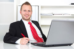 Business manager in office. Sitting with laptop and pen in hand Royalty Free Stock Image