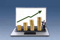 Business manager and profit growth coins chart. Business manager standing next to profit growth coins chart on blue background Royalty Free Stock Photos