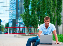Business manwith laptop in front of modern business building Royalty Free Stock Photo