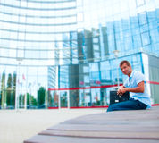 Business manwith laptop in front of modern business building Royalty Free Stock Image