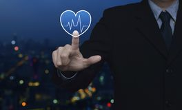 Business medical health care service concept. Heart beat pulse flat icon over blur colorful night light city tower and skyscraper, Business medical health care royalty free stock photography