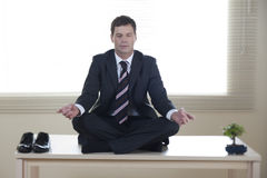 Business meditation. Young businessman meditating on his desk Royalty Free Stock Photos