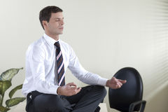 Business meditation. Young businessman meditating on his desk Royalty Free Stock Photo