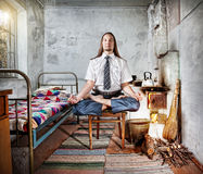 Business meditation. Businessman with long hair doing meditation in old Russian house with traditional stove Stock Photography