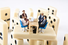Business meeting. Miniature figures in a business meeting on dominoes Royalty Free Stock Photos