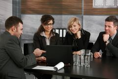 Business meeting. Young businesspeople having a meeting at table in office. Businessmen showing data on laptop computer, others looking at screen, smiling stock photography