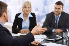 Business meeting. Businesspeople sitting at meeting table discussing work. Focus on hand stock photos