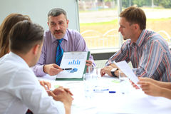 Business meeting. Manager discussing work with his colleagues Stock Images