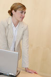 Business meeting. Young business woman stands over laptop in her office Royalty Free Stock Photos