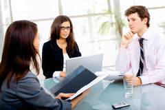 Business meeting. Three young businespeople working in team at office, smiling Stock Photography