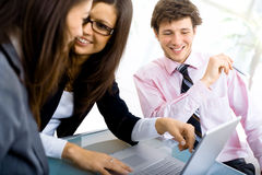 Business meeting. Three young businespeople working in team at office, smiling Stock Image