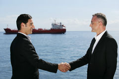 Business meeting. Businessmen shaking hands in front of a cargo boat Stock Images