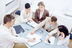 Business meeting. Five businesspeople sitting around table in office and having a meeting. Discussing business plans and writing notes on paper stock images