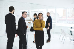 Business meeting while administrative calling to finish arrangements. Group of skilled male and female leaders of trading corporation meeting together in royalty free stock image