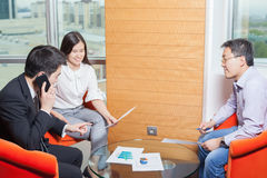 Business meeting Asian nationality people. Business meeting, Asian people sitting for a glass table with business plan on high floor in the office. Asian Royalty Free Stock Photo
