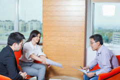Business meeting Asian nationality people. Business meeting, Asian people sitting for a glass table with business plan on high floor in the office. Asian Royalty Free Stock Photos