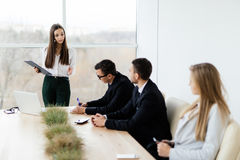 Business meeting. Business woman give notice for team while sitting together at the table stock images