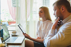 Business meeting in a cafe. Man and woman Looking at the laptop Stock Photos
