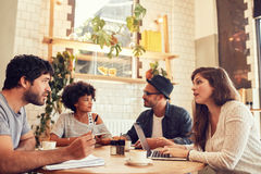 Business meeting at the coffee shop. Portrait of young people sitting in a coffee shop with laptop and talking. Young men and women discussing business ideas at Royalty Free Stock Photography